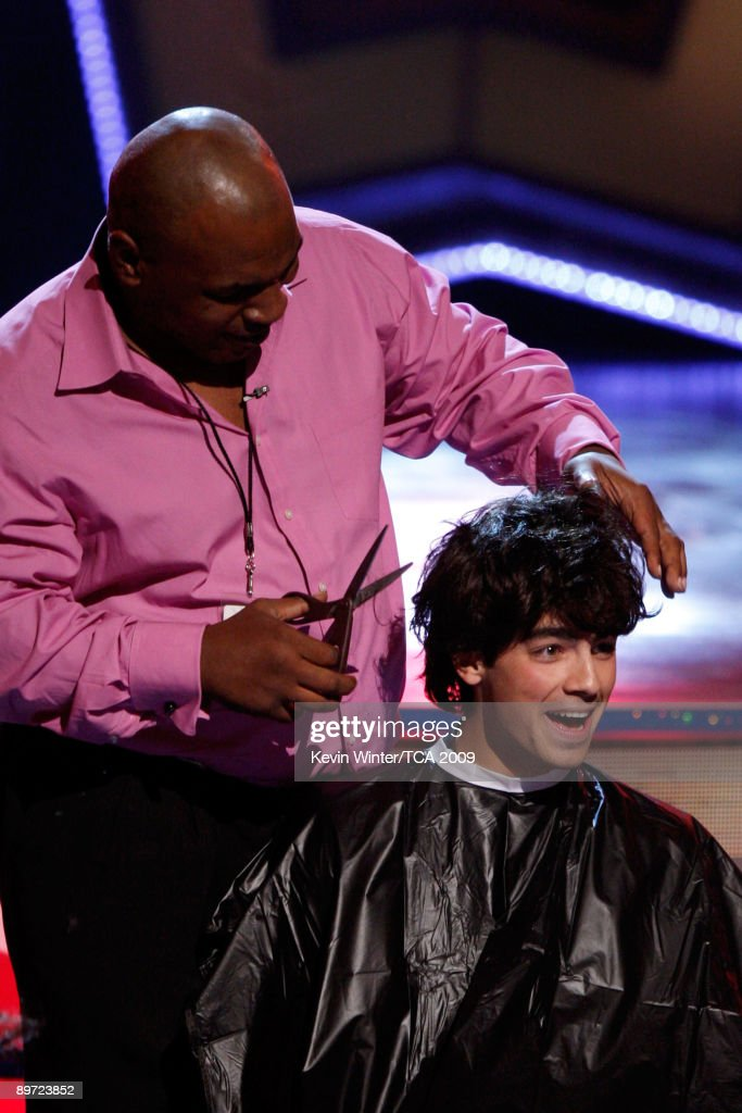 Boxer Mike Tyson cuts Musician Joe Jonas' hair onstage during the 2009 Teen Choice Awards held at Gibson Amphitheatre on August 9, 2009 in Universal City, California.