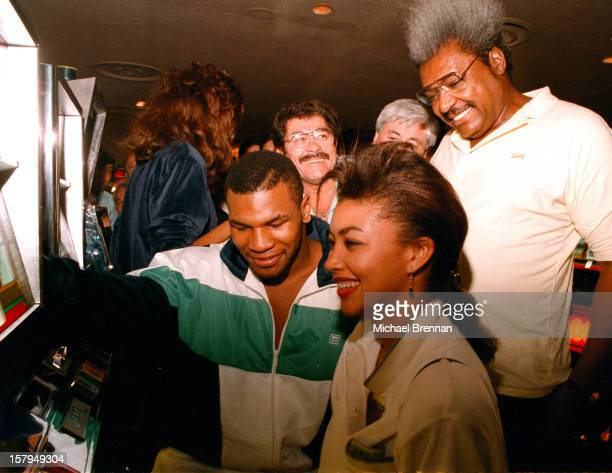 Boxer Mike Tyson surrounded by admirers and his promoter Don King plays the slot machines at the Hilton Hotel Casino Las Vegas Nevada December 1988...