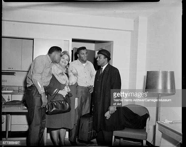 Boxer Muhammad Ali kissing his mother Odessa Grady Clay with his brother Rudy and father Davis Clay looking on in Carlton House Hotel Pittsburgh...