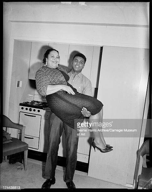 Boxer Muhammad Ali lifting his mother Odessa Grady Clay in room at Carlton House Hotel Pittsburgh Pennsylvania 1963