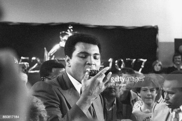 Boxer Muhammed Ali samples a cake which is specially made for him by children from Pendower Hall School in Newcastle The world heavyweight boxing...