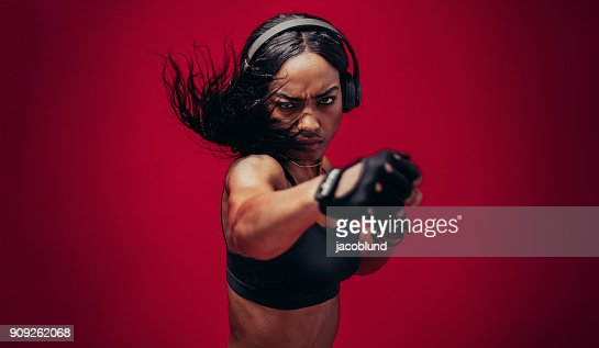 Boxer practicing her punches in a studio : Stock Photo