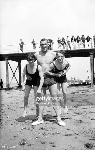 Boxer Primo Carnera holding two children in his arms during his training on the beach in January 1929 in the United States