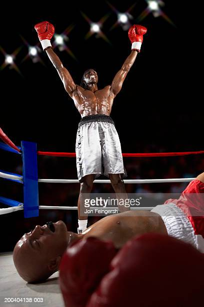 Boxer raising arms in victory over boxer on canvas