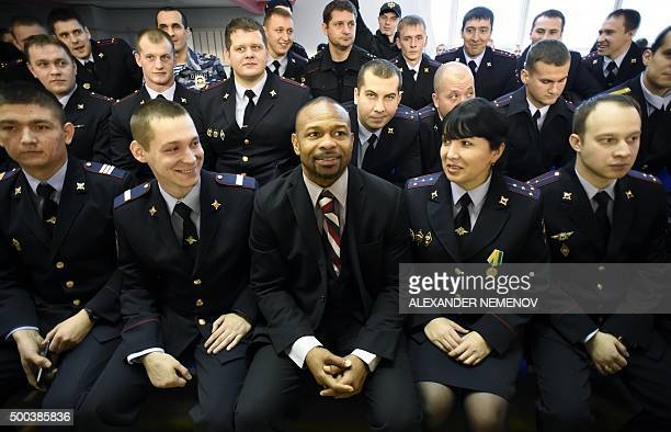 Boxer Roy Jones Jr who recently became a Russian citizen poses for pictures with Russia's police officers during his masterclass in Moscow on...