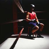 Boxer sitting in corner of boxing ring, portrait