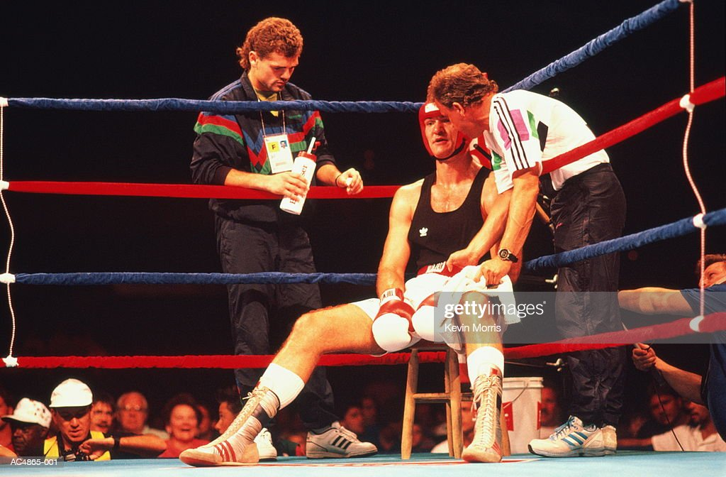 Boxer sitting in corner of ring with coach,trainer : Stock Photo