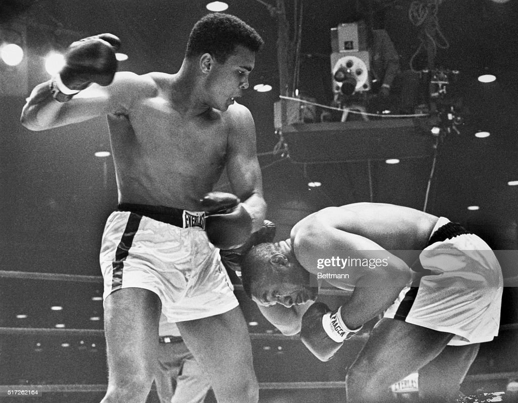 Boxer Sonny Liston ducks and covers up as Cassius Clay (later known as Muhammad Ali) aims a right at him during their title fight. Liston injured his shoulder early in the 1964 fight and lost the heavyweight title by a knockout in the seventh round.