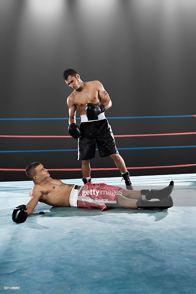 Boxer standing and opponent on floor : Stock Photo