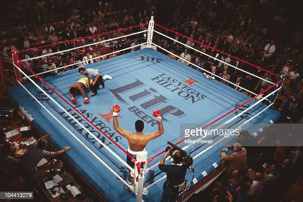 A boxer stands in a neutral corner arms aloft in victory as his opponent lays on the canvas and is counted out by the referee on 1st January 1986 at...
