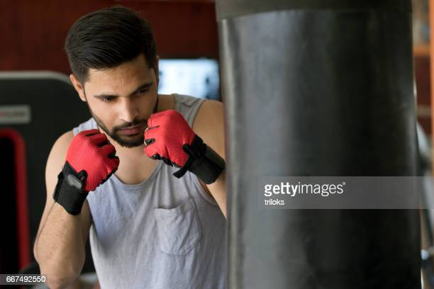 Boxer striking the punching bag at gym
