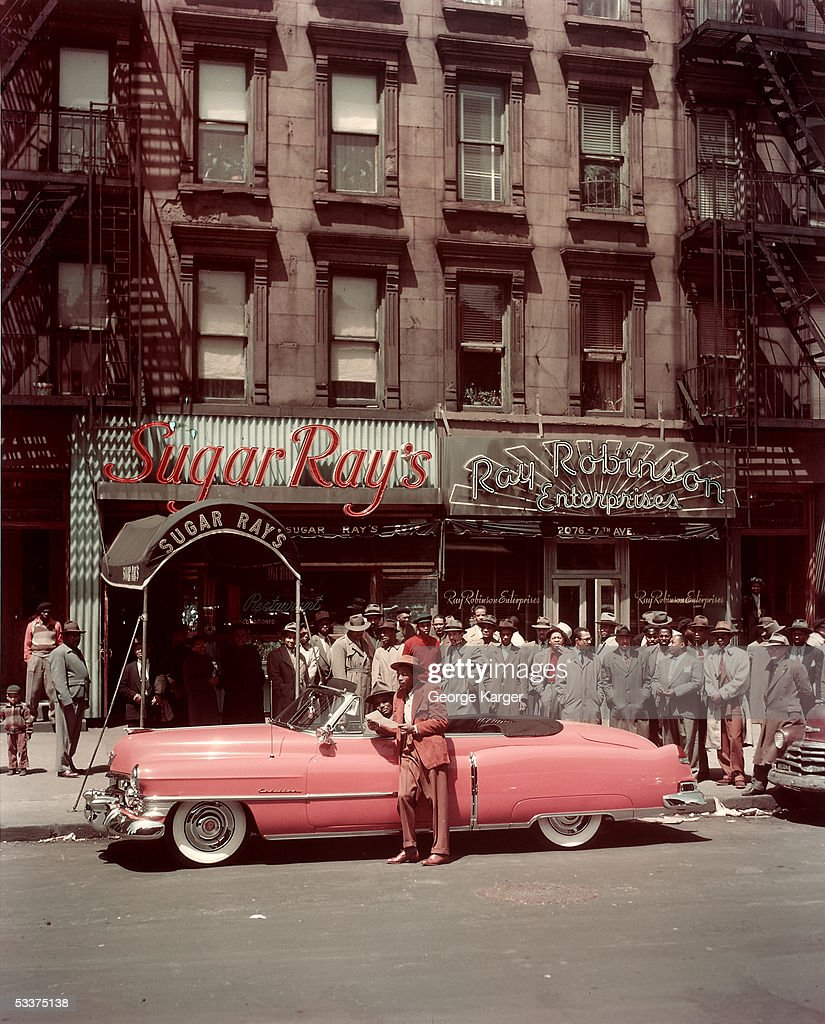 Boxer Sugar Ray Robinson leaning on his 1950 pink Cadillac convertible in front of two of his businesses in Harlem
