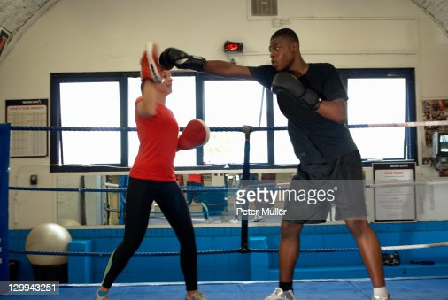 Boxer training with coach in ring : Stock Photo