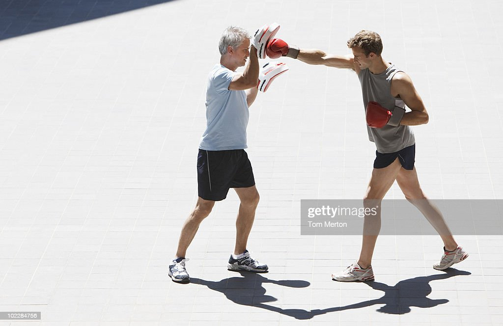 Boxer training with coach outdoors : Stock Photo