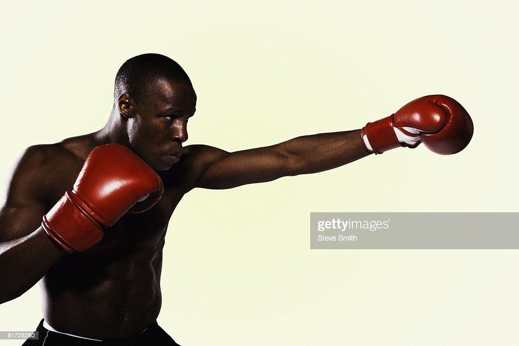 Boxer wearing gloves practicing punching : Stock Photo