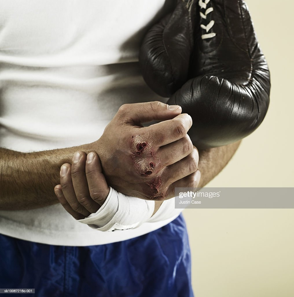 Boxer with scubs on knuckles, close up, mid section, studio shot : Stock Photo