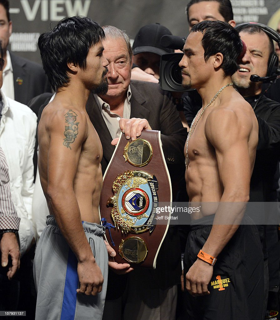 Boxers Manny Pacquiao (L) and Juan Manuel Marquez face off as Top Rank promoter Bob Arum holds the championship belt during the official weigh-in for their welterweight bout at the MGM Grand Garden Arena on December 7, 2012 in Las Vegas, Nevada. Pacquiao and Marquez will fight each other for the fourth time on Dec. 8 in Las Vegas.