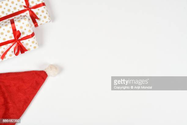 Boxes gifts wrapped in printed paper and red colored ribbons on white background, high angle view and copy space