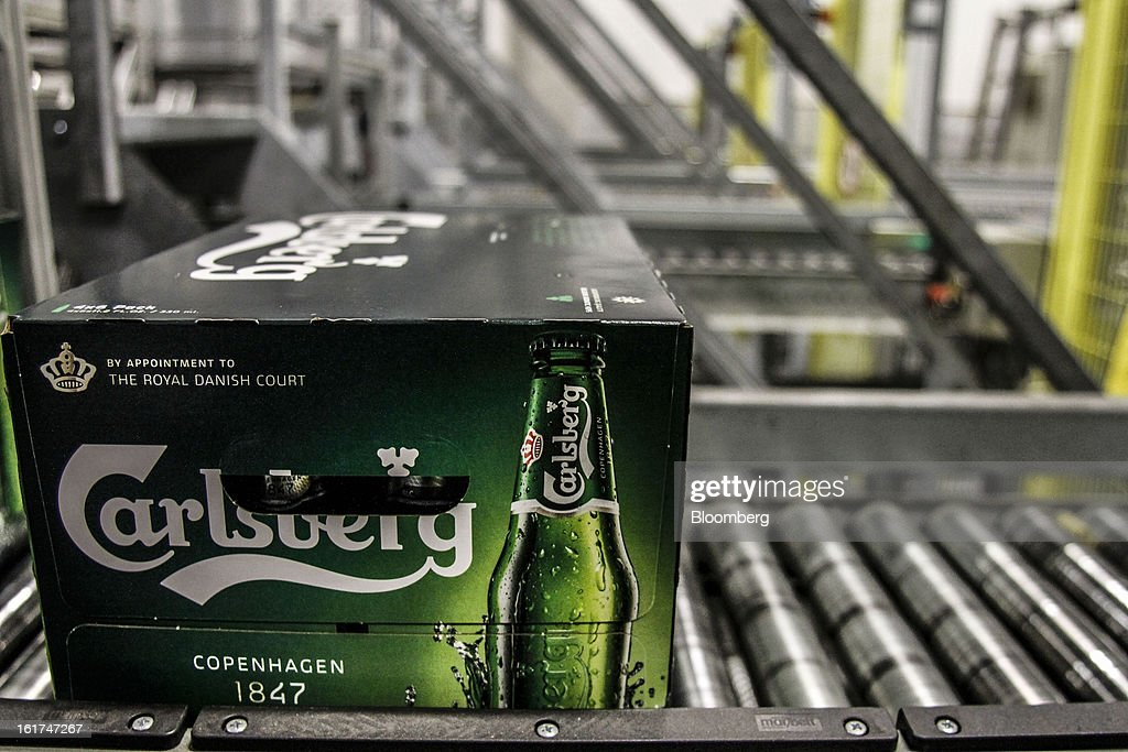Boxes of Carlsberg bottled beer move along a conveyor belt before an automated stacking process by machine for customer orders at the Carlsberg A/S East Terminal distribution depot in Tastrup, Denmark, on Thursday, Feb. 14, 2013. Danish brewer Carlsberg A/S owns France's biggest beer brand Kronenbourg. Photographer: Freya Ingrid Morales/Bloomberg via Getty Images
