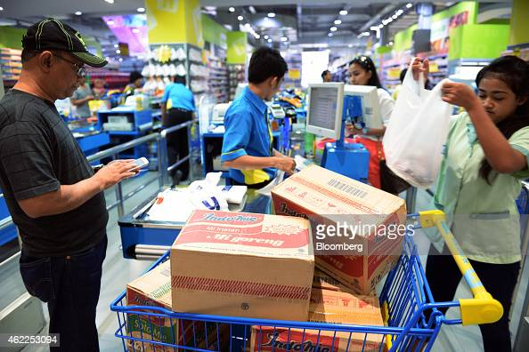 Boxes of Indomie fried noodles produced by PT Indofood Suskes Malmur Tbk sit in a shopping cart at a checkout counter at a Hypermart supermarket...