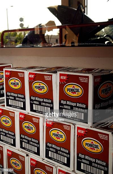 Boxes of Pennzoil motor oil are stacked near an employee of Jiffy Lube a company owned by PennzoilQuaker State Co changing performing an oil change...