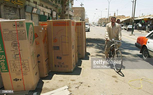 Boxes of refrigerators for sale crowd onto a street as a man on a bicycle rides by 09 July in the flashpoint town of Fallujah some 50kms west of...