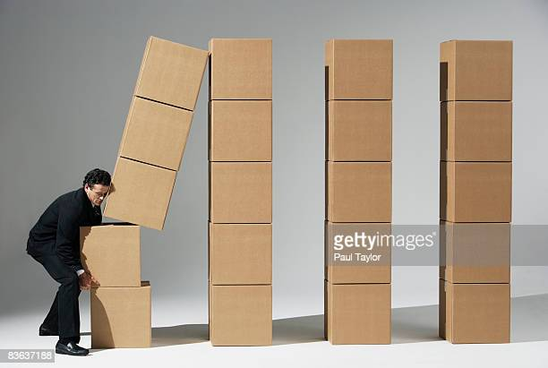 Boxes with man tipping stack
