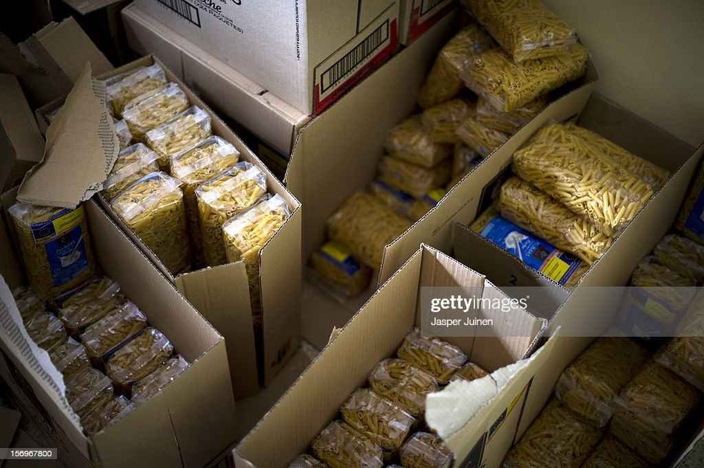 Boxes with pasta stand inside a Red Cross post ready to be handed out on November 23, 2012 in Villacanas, Spain. During the boom years, where in its peak Spain built some 800,000 houses a year accompanied by the manufacturing of millions of wooden doors where needed, the people of Villacanas were part of Spain's middle class enjoying high wages and permanent jobs. During the construction boom years the majority of the doors used within these new developments were made in this small industrial town. Approximately seven million doors a year were once assembled here and the factory employed a workforce of almost 5700 people, but the town is now left almost desolate with the Villacanas industrial park now empty and redundant. With Spain in the grip of recession and the housing bubble burst, Villacanas is typical of many former buoyant industrial Spanish towns now struggling with huge unemployment problems.