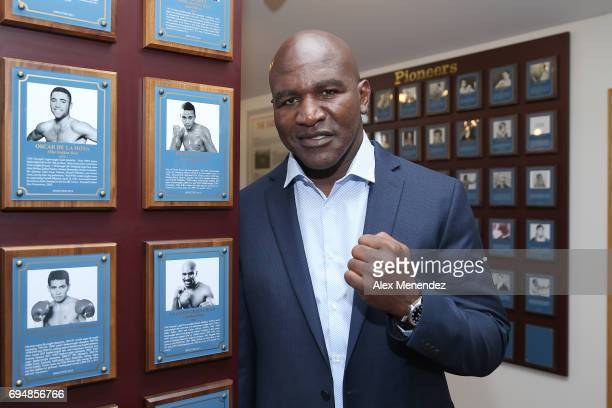 Boxing champion Evander Holyfield poses beside his plaque during the International Boxing Hall of Fame induction Weekend of Champions event on June...