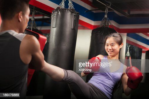 Boxing Couch Holding Pad While Smiling Female Student