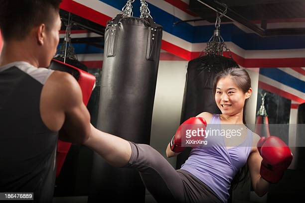Boxing couch holding pad while smiling female student kicks into it