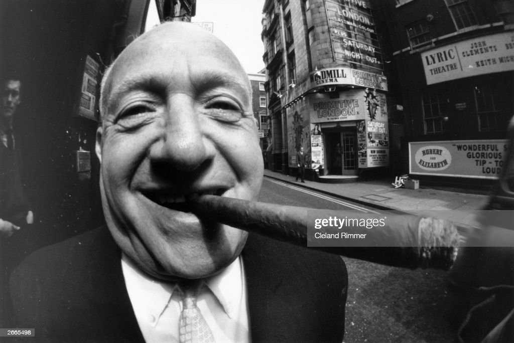 Boxing entrepreneur Jack Solomons enjoying a cigar. In the background are the Windmill Cinema and the Lyric Theatre in London's Soho.