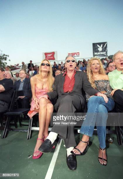 Feature Playboy founder Hugh Hefner sitting in the front row during boxing match with two of his closest playmates during fights at his Playboy...