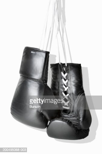 Boxing gloves hanging against white background, close-up