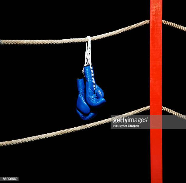 Boxing gloves hanging from boxing ring