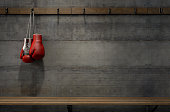 Spotlit boxing gloves hanging on a hanger above an empty wooden bench in a locker change room - 3D render