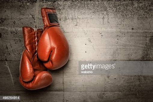 Boxing gloves hanging on concrete wall : Stock Photo