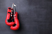 Boxing gloves hanging on black wall