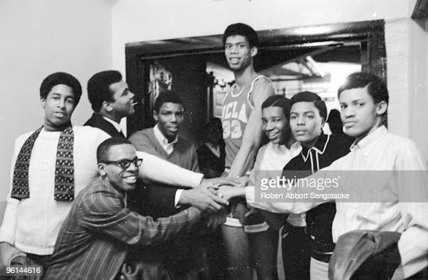 Boxing great Muhammad Ali back row second from left looks up and smiles at UCLA basketball player Kareem Abdul Jabbar back row center then known as...