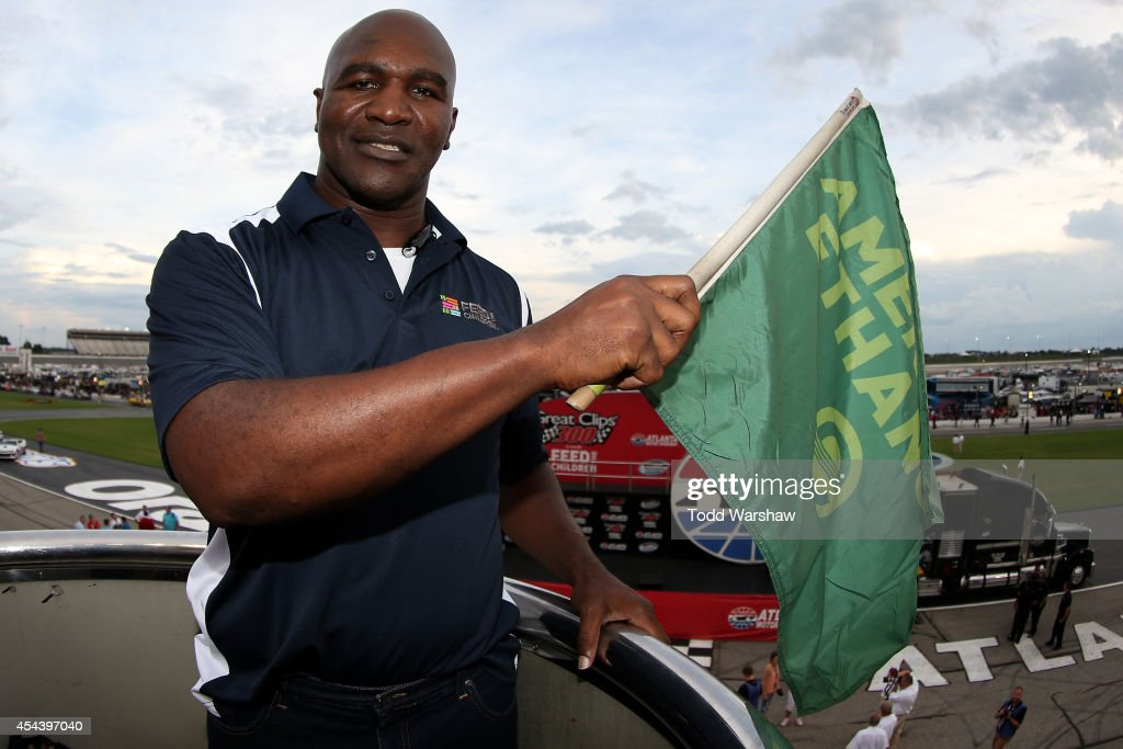 Boxing legend Evander Holyfield poses with the green flag prior to the start of the NASCAR Nationwide Series Great Clips 300 at Atlanta Motor Speedway on August 30, 2014 in Hampton, Georgia.