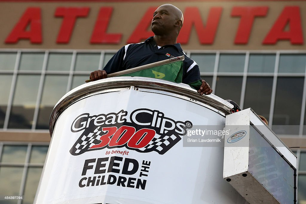Boxing legend Evander Holyfield stands in the flag stand prior to the start of the the NASCAR Nationwide Series Great Clips 300 at Atlanta Motor Speedway on August 30, 2014 in Hampton, Georgia.