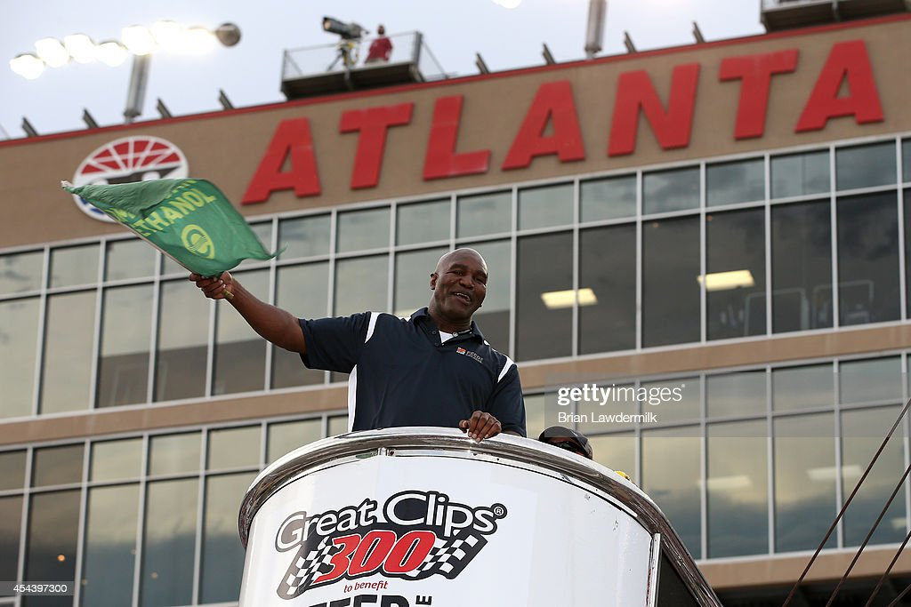 Boxing legend Evander Holyfield waves the green flag to start the the NASCAR Nationwide Series Great Clips 300 at Atlanta Motor Speedway on August 30, 2014 in Hampton, Georgia.