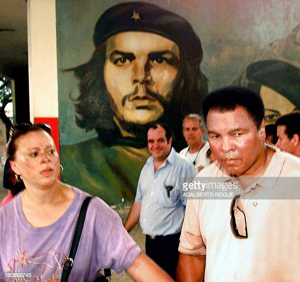 US boxing legend Muhammad Ali and his wife Lonnie Ali pass by a mural of Cuban revolutionary hero Ernesto 'Che' Guevara 10 September as they arrive...