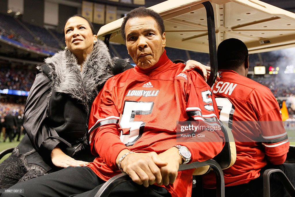 Boxing legend Muhammad Ali and his wife Lonnie Ali ride a golf cart onto the field to represent the Louisville Cardinals for the coin toss against the Florida Gators prior to the start of the Allstate Sugar Bowl at Mercedes-Benz Superdome on January 2, 2013 in New Orleans, Louisiana.