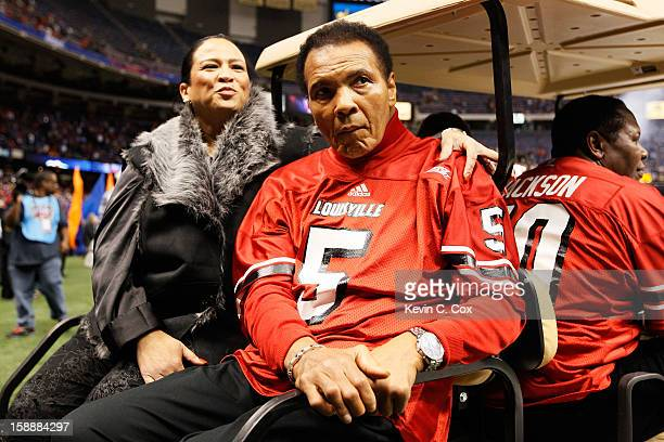 Boxing legend Muhammad Ali rides a golf cart onto the field to represent the Louisville Cardinals for the coin toss against the Florida Gators prior...
