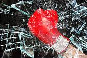 Boxing glove through broken glass window.