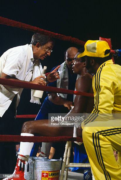 Boxing trainer Angelo Dundee left talks with his welterweight fighter Sugar Ray Leonard sitting in his corner in between rounds during a welterweight...