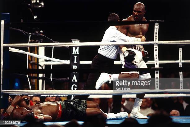 WBA/ IBF Heavyweight Title Evander Holyfield being held by referee Mitch Halpern after knockdown of Michael Moorer at Thomas Mack Center Las Vegas NV...