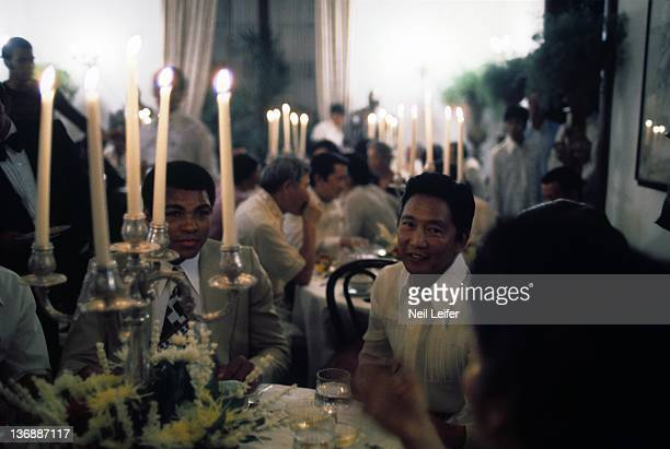 Boxing WBC/ WBA World Heavyweight Title Muhammad Ali dining with Filipino President Ferdinand Marcos during party after winning fight vs Joe Frazier...