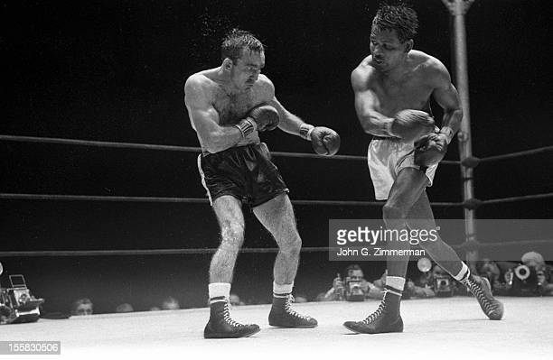 World Middleweight Title Carmen Basilio in action vs Sugar Ray Robinson during fight at Yankee Stadium Bronx NY CREDIT John G Zimmerman